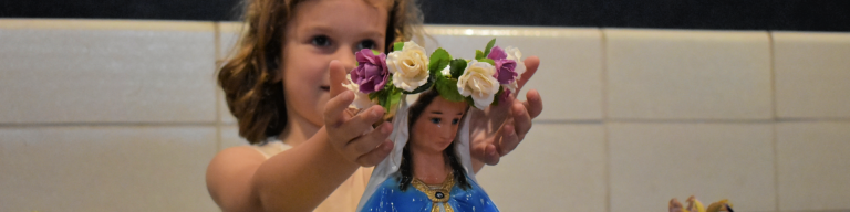 little girl places crown of roses on statue of virgin mary