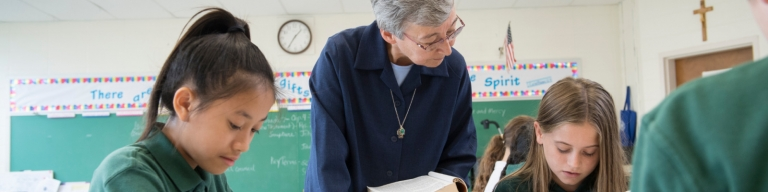 Sister Joan assisting female students with lesson