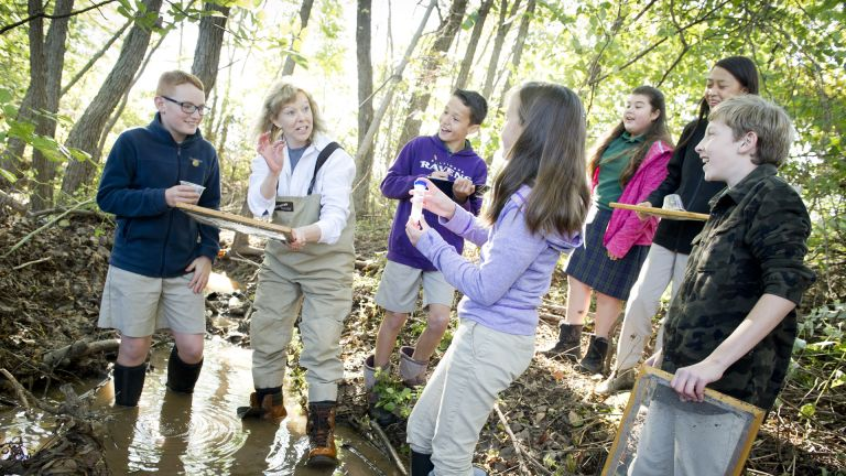 teacher with smiling students studying science in stream